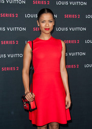 Gugu Mbatha-Raw matched her red dress with a boxy shoulder bag for the Louis Vuitton 'Series 2' exhibition.