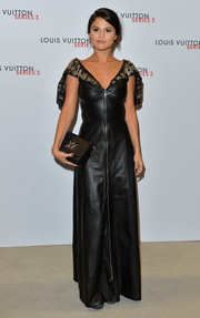 Selena Gomez wore a full-length black leather dress with studded cape detailing over her shoulders at a party for Louis Vuitton during London Fashion Week.