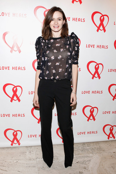Emily Mortimer paired a sheer black floral print blouse with puffy sleeves with a pair of casual black pants at the Love Heals Gala.