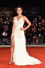 Penelope Cruz ravished in a white Atelier Versace halter gown with a feathered skirt and a hip-high slit at the Venice Film Festival premiere of 'Loving Pablo.'