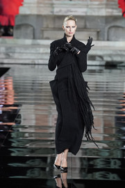 Karolina Kurkova hit the LuisaViaRoma CR runway wearing a fringed black wool coat by Yohji Yamamoto.