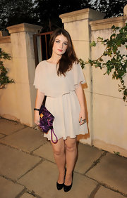 Eve Hewson offset her romantic chiffon dress at Miu Miu's 'Muta' presentation with a dazzling purple sequined Rococco pochette. The vibrant clutch injected a youthful vibe into her look.