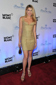 Meredith Ostrom accented her gold bandage dress with a petite glossy frame clutch.