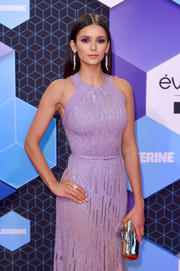 Nina Dobrev attended the MTV EMAs carrying a gold tube clutch by Jimmy Choo.