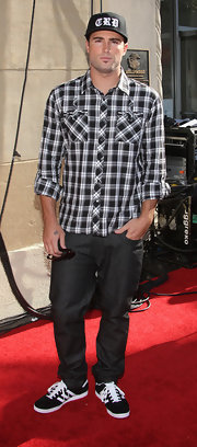 Brody Jenner paired his back jeans with a plaid button up.
