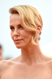 Charlize Theron styled her hair with a wavy tendril down one side and a twisted bun at the back for the 'Mad Max: Fury Road' premiere in Cannes.