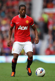 Patrice Evra handles the ball with his Nike cleats (and bright orange laces).