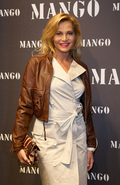 Simona Ventura looked totally chic in a cropped brown leather jacket layered over a white coat dress.