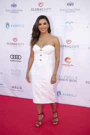 Eva Longoria styled her frock with red wave-strap sandals by Prada.