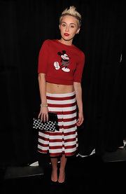 Miley Cyrus showed off her midriff by pulling down her striped knee-length skirt and wearing it around her hips.