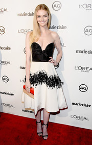 For a pop of color, Lydia Hearst accessorized with an orange and beige hard-case clutch.