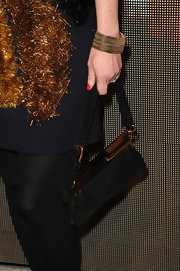 Shirley Manson carried a classic black leather evening bag with gold metal hardware that complemented her retro look.