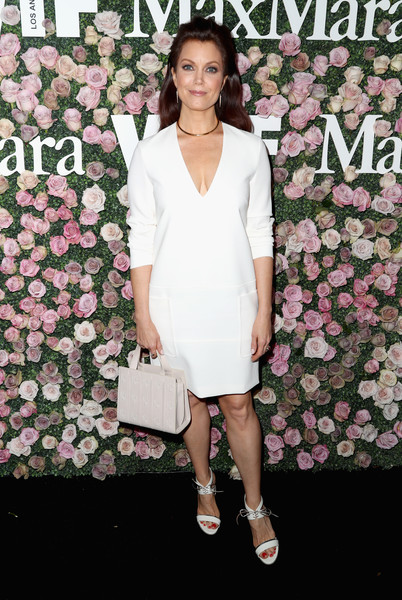 Bellamy Young accessorized with a cream-colored embossed-leather purse.