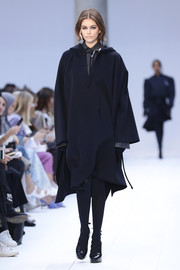 Kaia Gerber matched her cape with black tights.
