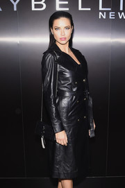 Adriana Lima teamed a black YSL chain-strap bag with a leather trenchcoat for the Maybelline NYFW welcome party.