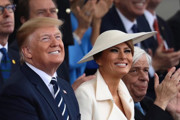 Melania Trump Wide Brimmed Hat [event,crowd,gesture,headgear,smile,hat,white-collar worker,fashion accessory,first lady,president,donald trump,commemoration,united states,portsmouth,british,uk,d-day,world war ii]