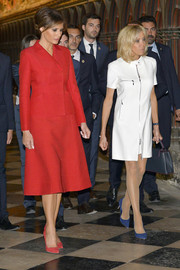 Brigitte Macron styled her LWD with a pair of blue suede pumps.