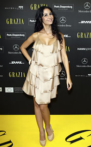 Sila Sahin looked fab and flirty in a tiered gold cocktail dress.