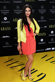 Sila Sahin wore a brightly colored ensemble at Berlin Fashion Week, consisting of an orange mini-dress and a yellow blazer.