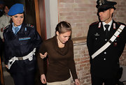 Here, Amanda Knox wore a brown sweater and khaki slacks.
