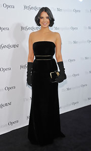 Olivia expresses her elegance with black evening gloves and a velvet gown at the Metropolitan Gala.