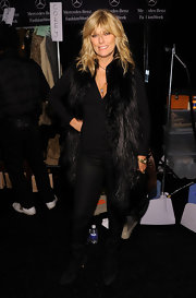 At the Michael Kors Fall 2012 fashion show during Mercedes-Benz Fashion Week, Patti Hansen complemented her head-to-toe black outfit with a matching black oversize fur vest.