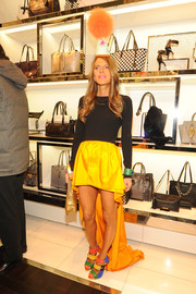 Anna dello Russo turned plenty of heads with her black and bright-yellow Michael Kors fishtail dress, teamed with a pompom hat, at the Michael Kors Milano cocktail party.