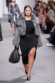 Ashley Graham flashed some leg in a high-slit black knit dress while walking the Michael Kors runway.