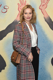 Eva Herzigova attended the Michael Kors fashion show carrying a tan shoulder bag with a gold chain strap.
