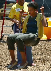 Michelle Obama complemented her casual outfit with girly gold ballet flats as she helped build a playground at a DC school.