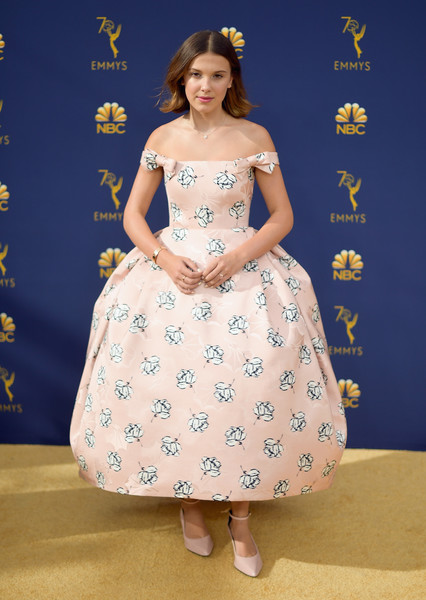Millie Bobby Brown Off-the-Shoulder Dress [clothing,dress,lady,shoulder,fashion,fashion model,gown,joint,pattern,neck,arrivals,millie bobby brown,emmy awards,70th emmy awards,microsoft theater,los angeles,california,regina king,70th primetime emmy awards,stranger things,primetime emmy award,emmy award,eleven,2018 brit awards,2018,red carpet]