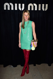 Anna dello Russo worked a striking color combo, pairing her green dress with red patent thigh-high boots.