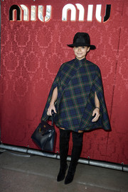 Miroslava Duma was uniquely styled, as always, in an A.W.A.K.E. plaid cape and over-the-knee boots during the Miu Miu fashion show.
