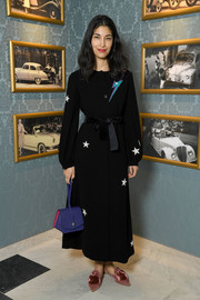 Caroline Issa rounded out her look with a purple leather wristlet.