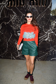 Bip Ling looked funky at the Miu Miu fashion show in green leather shorts and an embellished orange sweater.