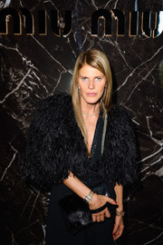 Anna dello Russo finished off her elaborate all-black ensemble with a fur/snakeskin clutch when she attended the Miu Miu fashion show.