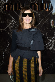 Carine Roitfeld donned a deconstructed-chic gray top and a striped pencil skirt for the Miu Miu fashion show.