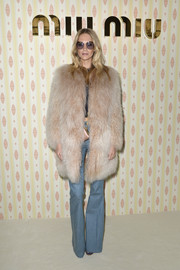 Poppy Delevingne was gangster-glam in a shaggy beige fur coat at the Miu Miu fashion show.