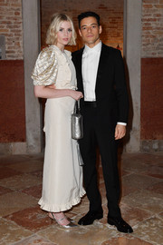 Lucy Boynton attended the Miu Miu Women's Tales dinner wearing an ivory dress with puffed sleeves and ruffle detailing.