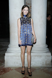 Mia Goth rounded out her look with a silver matelasse clutch by Miu Miu.