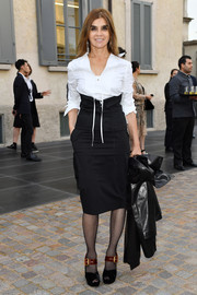Carine Roitfeld teamed a white lace-up blouse with a black pencil skirt and a corset belt for the Prada private dinner.