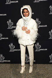 Miroslava Duma looked both fun and glam in a hooded white down jacket with crystal embellishments and feathered cuffs during the Moncler Grenoble presentation.