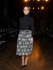 Emmy Rossum flaunted her tiny frame in a skintight black turtleneck by Wolford at the Monse fashion show.