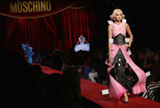 Gigi Hadid was all about whimsical glamour in this pink and black gown while walking the Moschino runway.