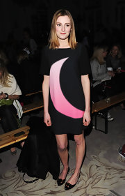 Laura Carmichael attended the Moschino LFW presentation wearing a short dress with a pink crescent moon print.