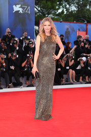Michelle Pfeiffer coordinated her dress with a black and gold tube clutch by Tod's.