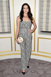 Laura Prepon paired her outfit with an adorable face-print clutch.