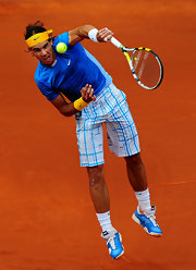 Refael Nadal dominates while wearing a bright yellow Nike headband.