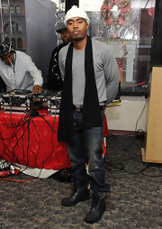 Nas accessorizes with a long black knit scarf.