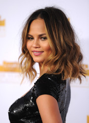 Chrissy Teigen attended the Sports Illustrated Swimsuit Issue 50th anniversary bash wearing her hair in messy-sexy waves.